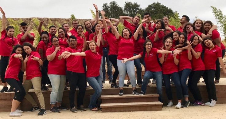 A group of students in matching red polos pose for a picture.